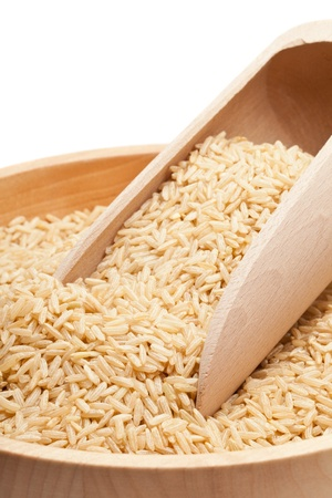 brown rice: Raw organic brown rice in wooden bowl over white background
