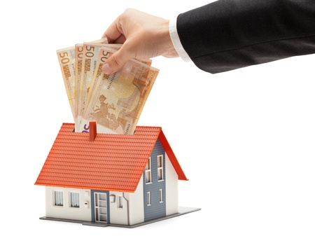 Man putting Euro banknotes into model house - real estate investment concept Stock Photo