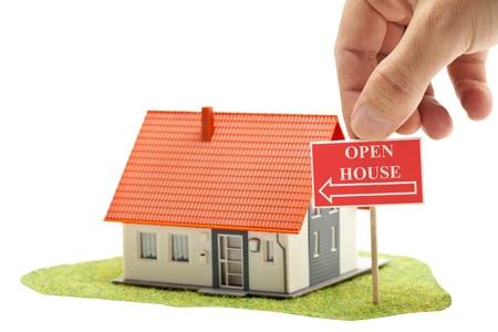"""open huis: Hand met """"open huis""""-teken in de voorkant van het model huis - onroerend goed concept"""