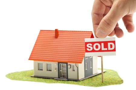 """Hand die """"verkocht""""-teken in de voorkant van het model huis - onroerend goed te kopen begrip Stockfoto"""