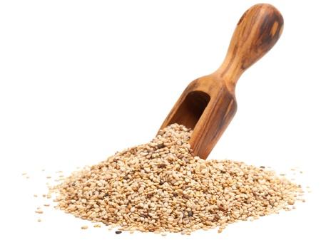 Semi di sesamo organico con paletta di legno su sfondo bianco