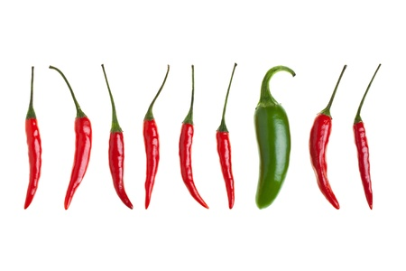 Birds eye chilis and one jalapeno chili in a row isolated on white background photo