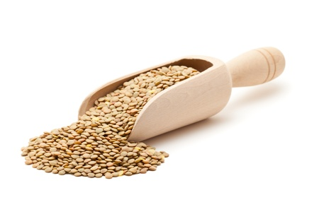 unprocessed: Uncooked lentils in wooden scoop over white background Stock Photo