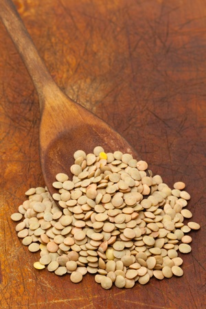 lentil: Raw organic lentils in wooden spoon over wood background Stock Photo