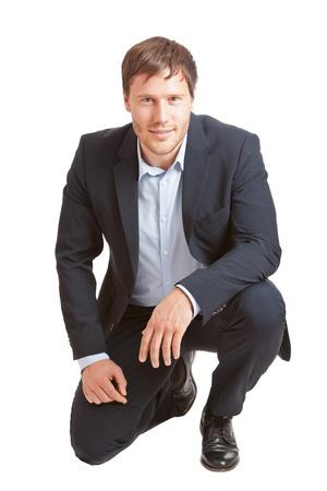 arrodillarse: Hombre de éxito empresarial joven y sonriente a la cámara sobre fondo blanco