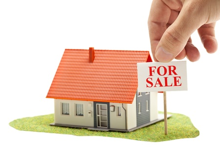 Hand holding 'for sale'-sign in front of model house - real estate buying concept photo