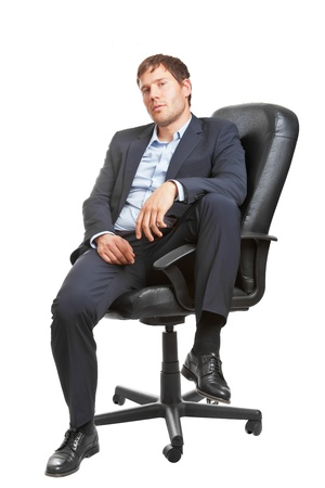 Young business man in office chair looking sceptical; isolated on white background photo