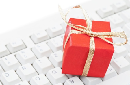Red present on computer keyboard - christmas online shopping concept photo