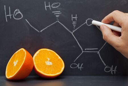 vitamin c: Hand drawing structural formula of vitamin C on blackboard with oranges in front Stock Photo