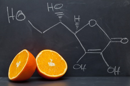 vitamins: Structural formula of vitamin C on blackboard with orange Stock Photo