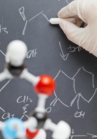 Chercheur écrit sur le tableau noir avec le modèle molécule au premier plan