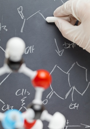 chemistry formula: Researcher writing on blackboard with molecule model in the foreground