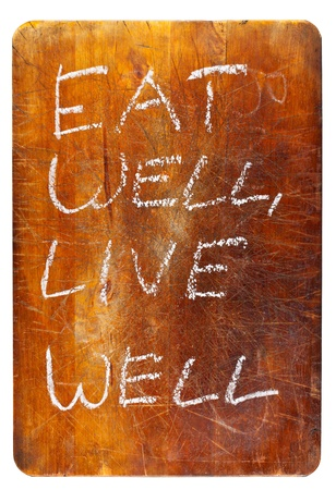 Eat well, live well text on wooden cutting board isolated on white background photo