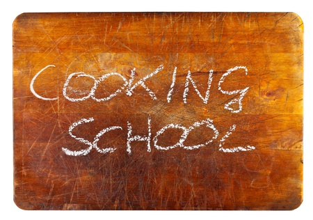 Cooking school text on wooden cutting board isolated on white background photo