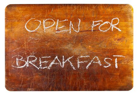 Open for breakfast text on wooden cutting board isolated on white background photo