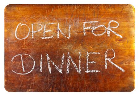 Open for dinner text on wooden cutting board isolated on white background photo