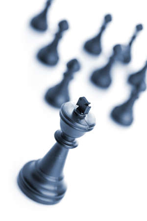 chess game: King chess figure in front of team over white background