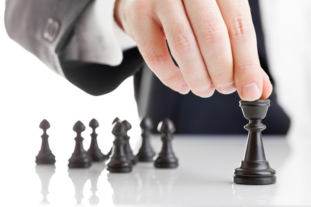 kavram: Business man moving chess figure with team behind - strategy or leadership concept Stok Fotoğraf