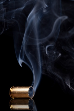 the casing: Smoking 9mm bullet casing over black background Stock Photo