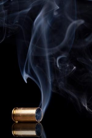 ammunition: Smoking 9mm bullet casing over black background Stock Photo