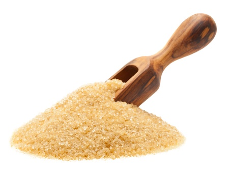 sugar: Heap of organic brown cane sugar with woden scoop over white background