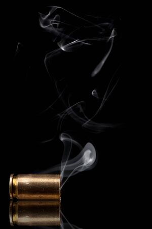 9mm: Smoking 9mm bullet casing over black background Stock Photo
