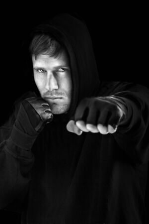 hit man: Young caucasian man boxing; isolated on black background Stock Photo