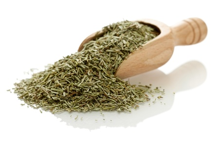 Dried rosemary leaves in wooden scoop over white background Stock Photo