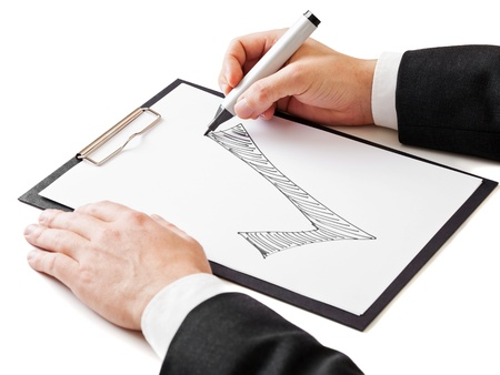 Businessman draws large checkmark on paper on clipboard; achievement or success concept; focus on tip of the pen photo