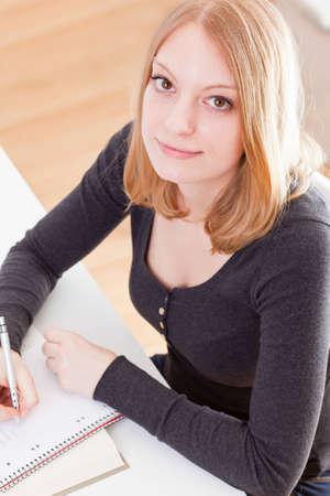 Joven estudiante mujer haciendo sus deberes en la mesa Foto de archivo - 12797758