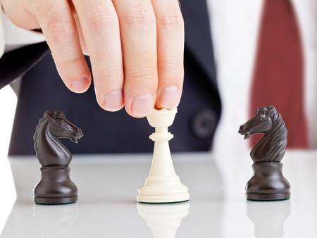 Business man holding chess queen figure between two arguing knight figures - conflict management concept Stock Photo