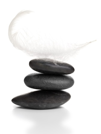 White feather on stack of black pebbles over white background - balance, stability or equilibrium concept photo