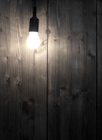Glowing lightbulb in front of wooden wall with copyspace - inspiration or idea concept Foto de archivo