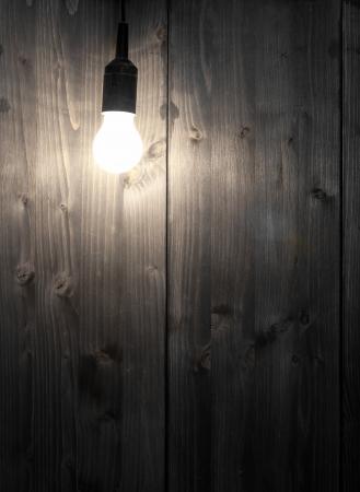 Leuchtende Glühbirne vor der Holzwand mit copyspace - Inspiration oder Idee Konzept Lizenzfreie Bilder