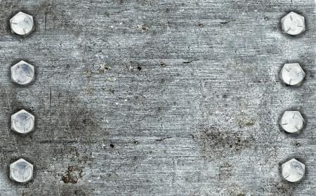 Hintergrund aus gebürstetem Metall mit zwei Reihen von Schrauben Standard-Bild