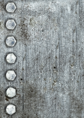 Brushed metal background with a row of bolts Stock Photo