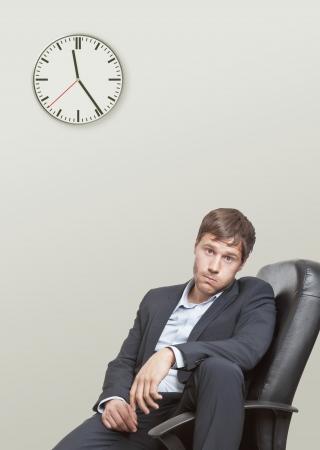 Frustriert jungen Geschäftsmann, der auf das Ende des Arbeitstages Lizenzfreie Bilder - 14433305