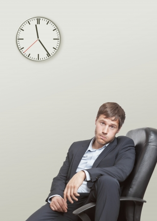 decepción: Hombre frustrado de negocios de jóvenes esperando el final de la jornada laboral