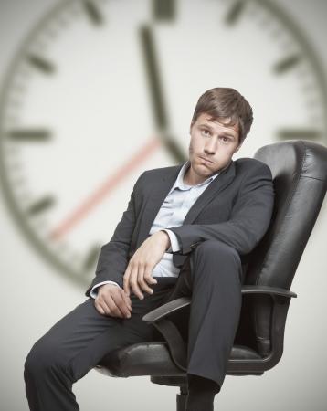 jornada de trabajo: Hombre frustrado de negocios de jóvenes esperando el final de la jornada laboral