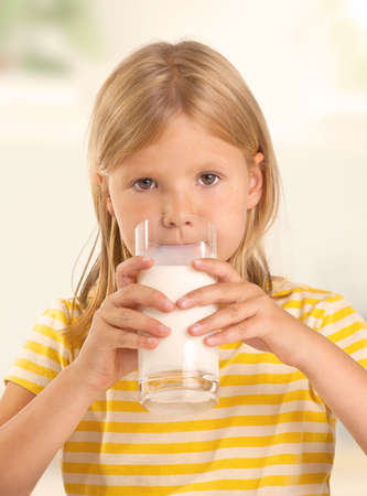 Cute young girl drinking a glass of milk photo