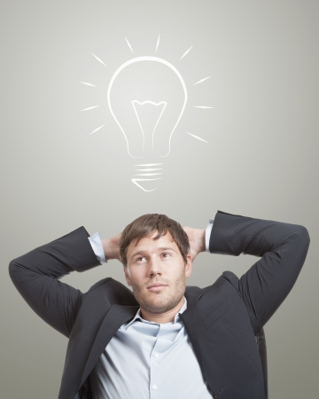 Business man in chair thinking with a light bulb over his head Stock Photo - 14679817