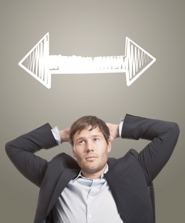 Business man in chair thinking with arrows in different directions over his head photo