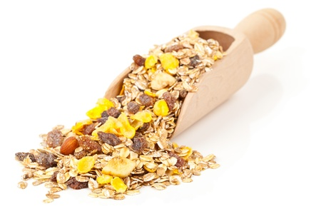 Muesli with dried fruits in wooden scoop isolated on white background photo