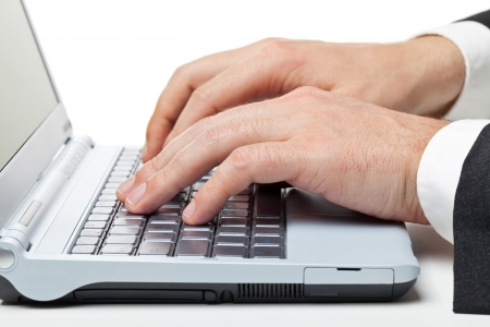 Businessman typing on laptop writing a document photo