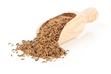 Les graines de cumin cumin dans écope en bois sur fond blanc