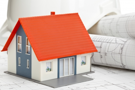 Model house on construction blueprints layed out on table