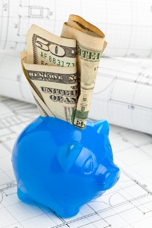home plans: Blue piggybank with dollar bills on home construction plans - home building financing concept