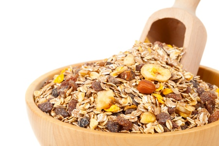 Muesli with dried fruits in wooden bowl isolated on white background photo