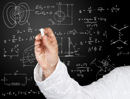 Research scientist writing physics diagrams and formulas with chalk on blackboard photo