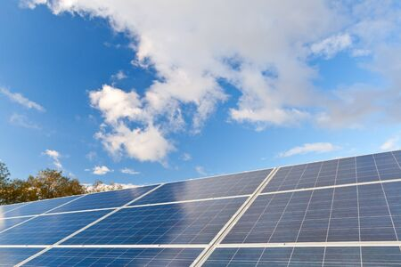 pv: Solar photovoltaics panels field for renewable energy production with blue sky and clouds